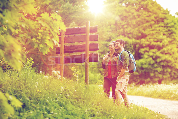 smiling couple at signpost with backpacks hiking Stock photo © dolgachov