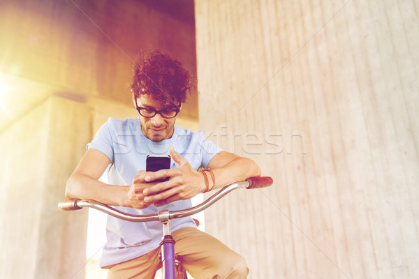 Stock photo: man with smartphone and fixed gear bike on street
