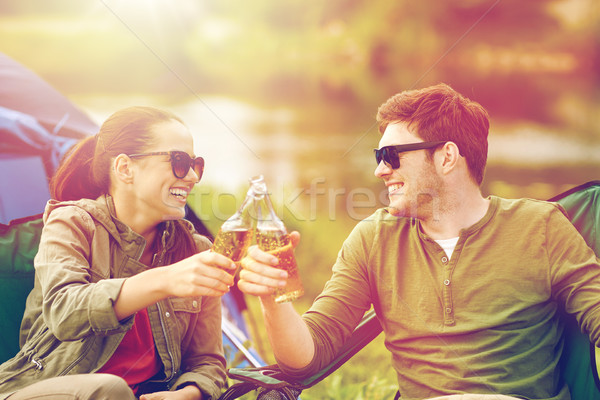 happy couple clinking drinks at campsite tent Stock photo © dolgachov
