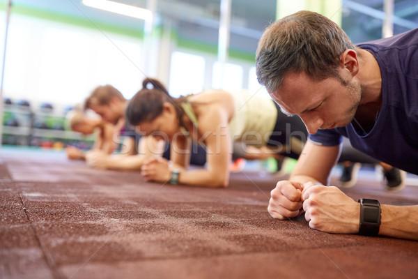 man at group training doing plank exercise in gym Stock photo © dolgachov