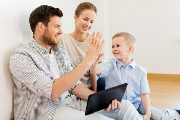 family with tablet pc at new home making high five Stock photo © dolgachov