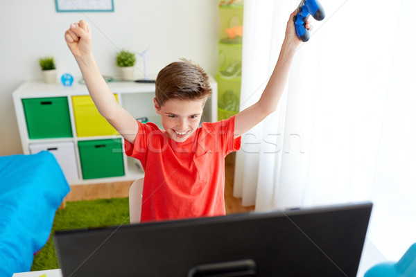 boy with gamepad playing video game on computer Stock photo © dolgachov