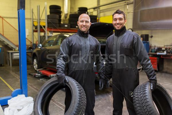 auto mechanics changing car tires at workshop Stock photo © dolgachov