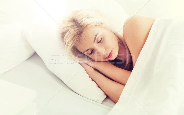 young woman sleeping in bed at home bedroom Stock photo © dolgachov