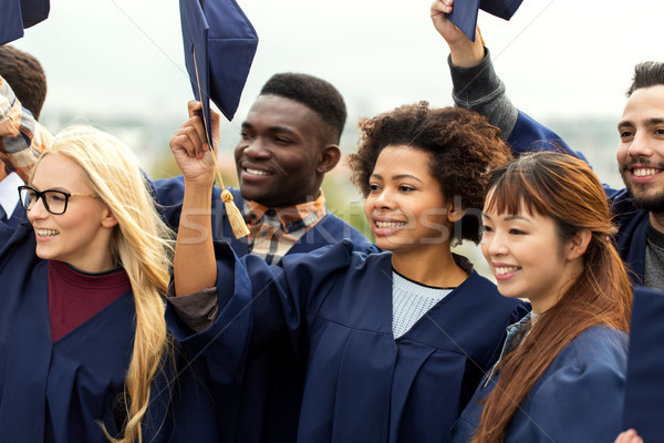 happy graduates or students waving mortar boards Stock photo © dolgachov