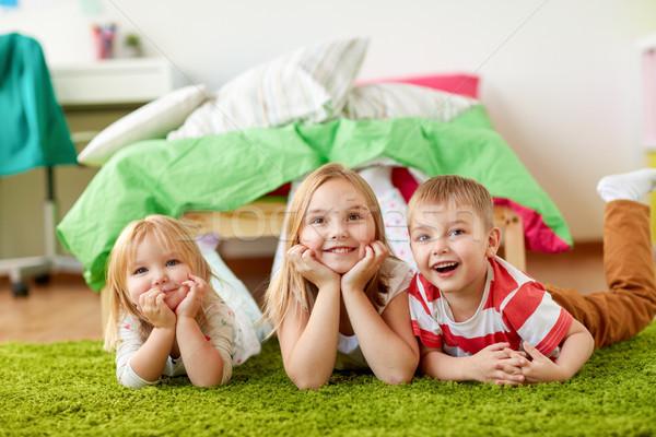 happy little kids lying on floor or carpet Stock photo © dolgachov