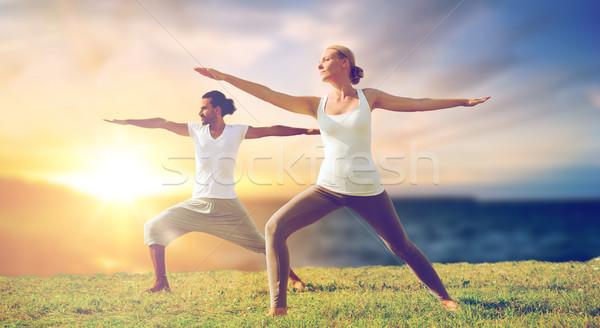 Paar yoga krijger pose buitenshuis Stockfoto © dolgachov