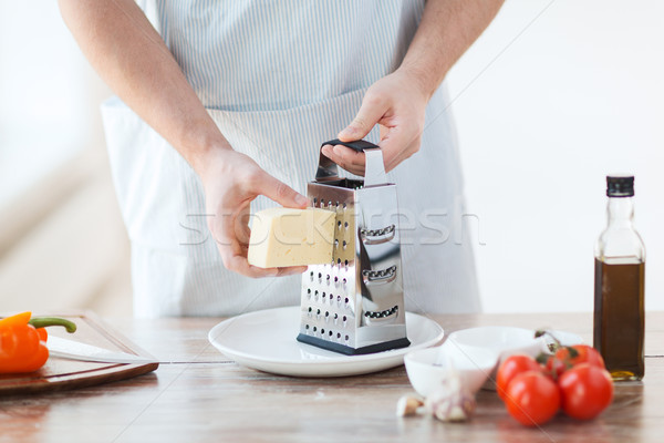 close up of male hands grating cheese Stock photo © dolgachov