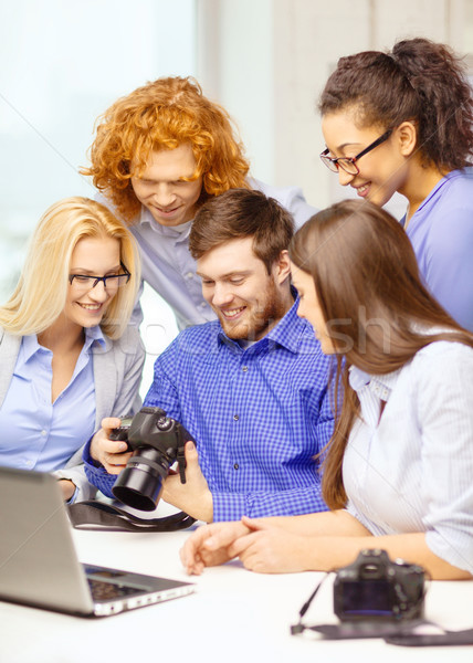 smiling team with laptop and photocamera in office Stock photo © dolgachov