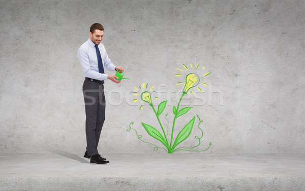 handsome businessman with green watering can Stock photo © dolgachov