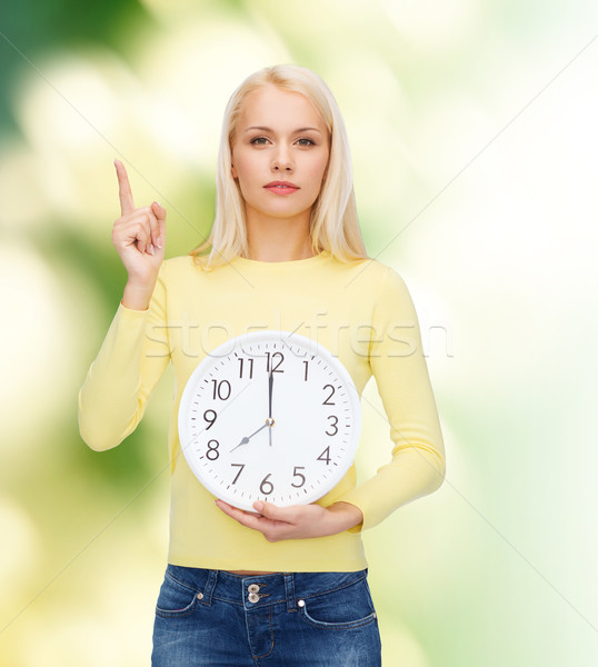 student with wall clock and finger up Stock photo © dolgachov