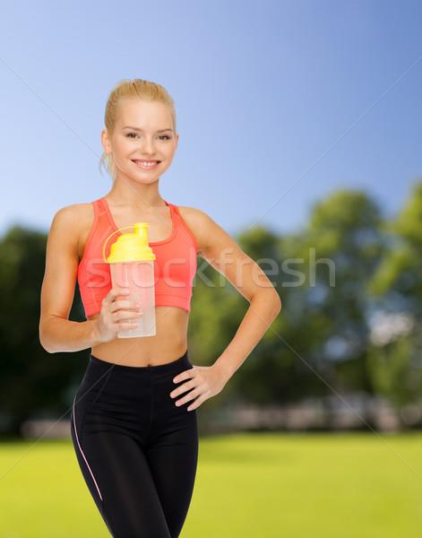 Gülen kadın protein sallamak şişe Stok fotoğraf © dolgachov