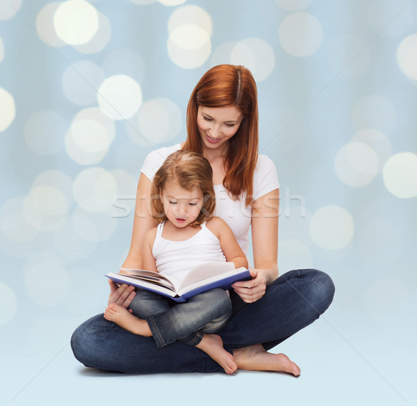 happy mother with adorable little girl and book Stock photo © dolgachov