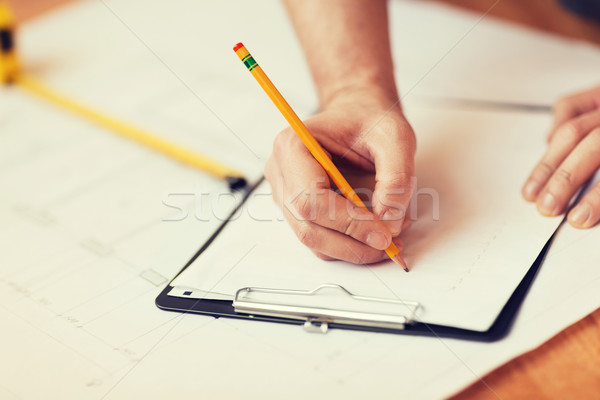 close up of male hands writing in clipboard Stock photo © dolgachov