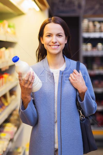 happy woman holding milk bottle in market Stock photo © dolgachov