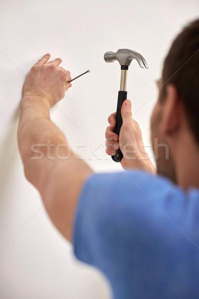 close up of man with hammer hammering nail in wall Stock photo © dolgachov