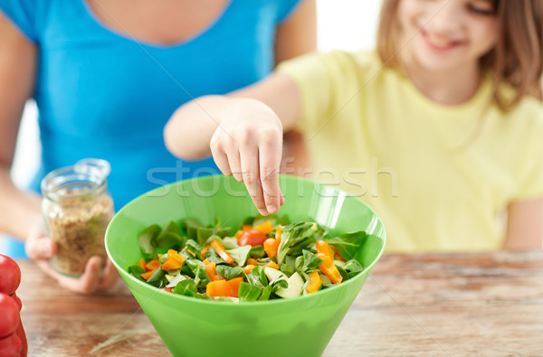 close up of happy family cooking salad in kitchen Stock photo © dolgachov