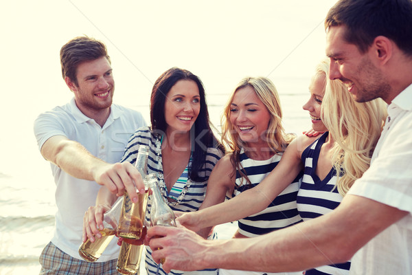 smiling friends clinking bottles on beach Stock photo © dolgachov