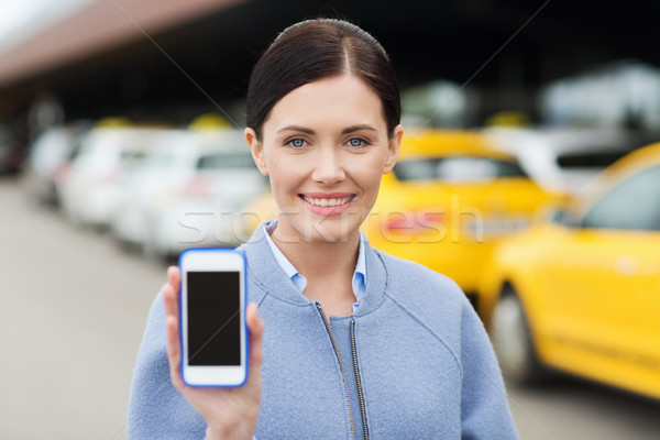 smiling woman showing smartphone over taxi in city Stock photo © dolgachov