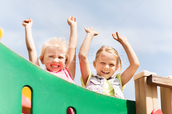 happy girls waving hands on children playground Stock photo © dolgachov