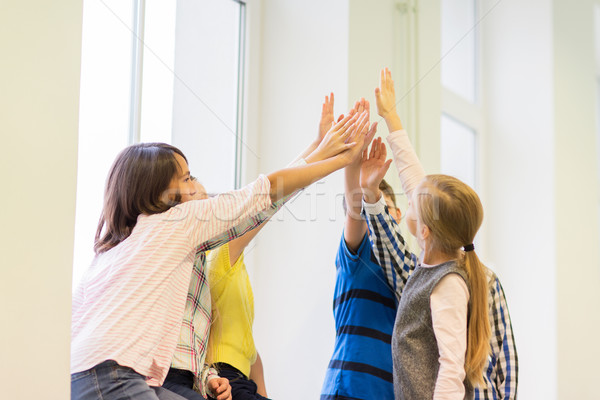 group of school kids making high five gesture Stock photo © dolgachov