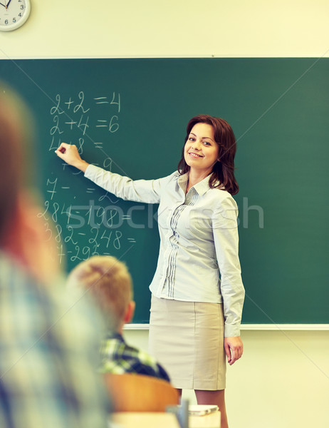 Stock photo: school kids and teacher writing on chalkboard