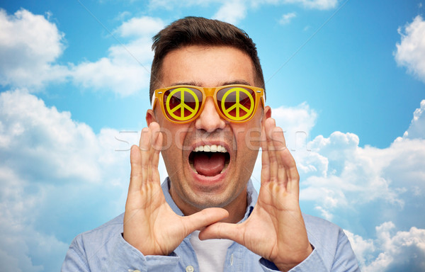 face of shouting man in green peace sunglasses Stock photo © dolgachov