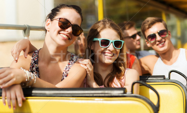 group of smiling friends traveling by tour bus Stock photo © dolgachov