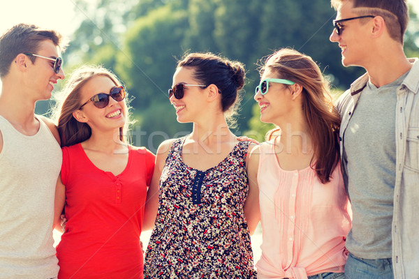 group of smiling friends in city Stock photo © dolgachov
