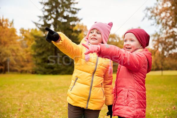 Boldog kislányok mutat ujj ősz park Stock fotó © dolgachov
