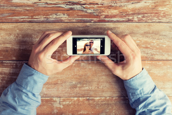 close up of male hands with photo on smartphone Stock photo © dolgachov