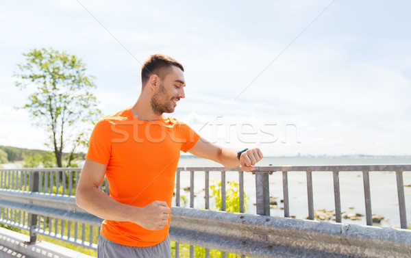 smiling young man with smart wristwatch at seaside Stock photo © dolgachov