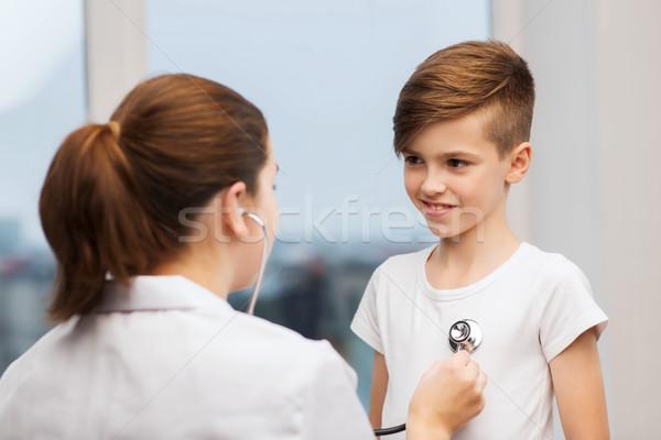 doctor with stethoscope listening to happy child Stock photo © dolgachov