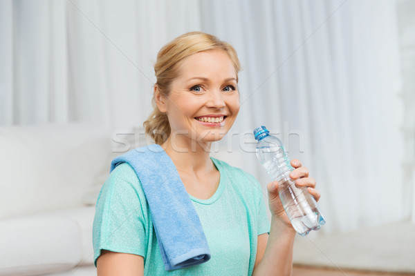 happy woman drinking water and exercising at home Stock photo © dolgachov