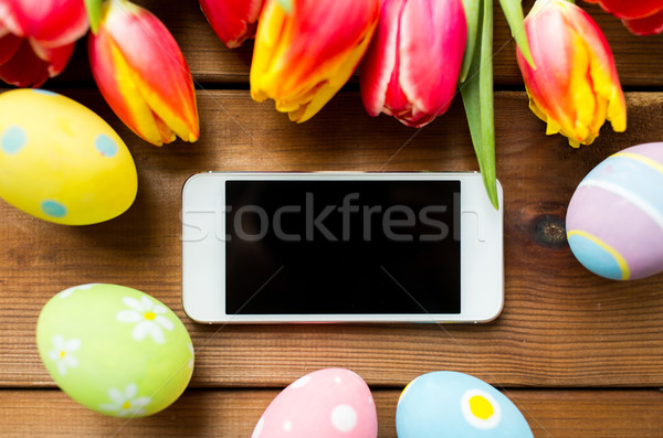 close up of easter eggs, flowers and smartphone Stock photo © dolgachov
