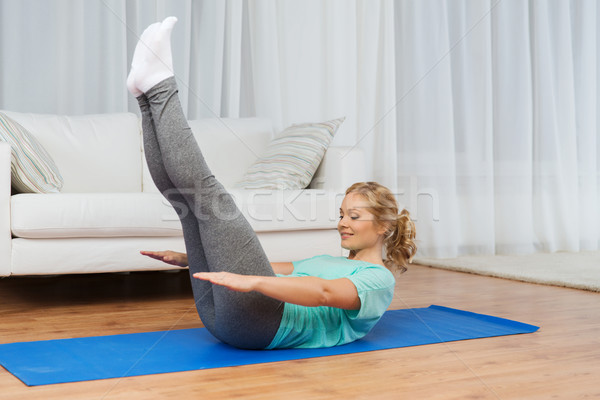 woman exercising on mat at home Stock photo © dolgachov