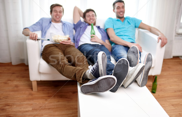 close up of male friends watching tv at home Stock photo © dolgachov