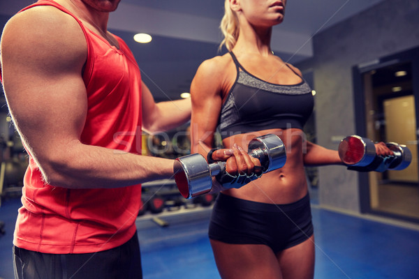young couple with dumbbell flexing muscles in gym Stock photo © dolgachov