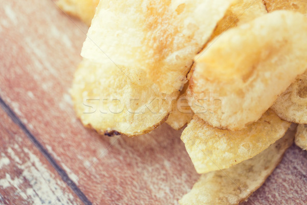 close up of crunchy potato crisps on wooden table Stock photo © dolgachov