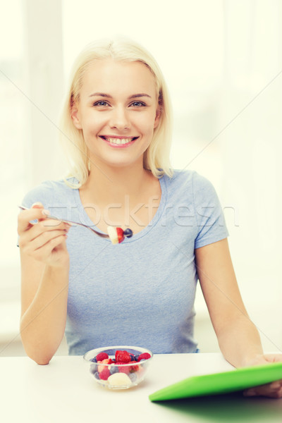 smiling woman eating fruits with tablet pc at home Stock photo © dolgachov