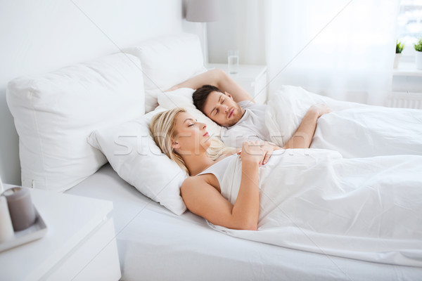 Stock photo: happy couple sleeping in bed at home