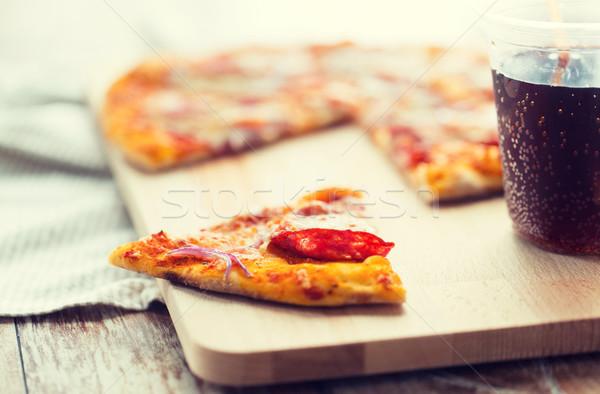 Közelkép pizza szénsavas ital asztal gyorsételek Stock fotó © dolgachov