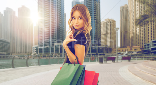 happy woman with shopping bags over dubai city Stock photo © dolgachov