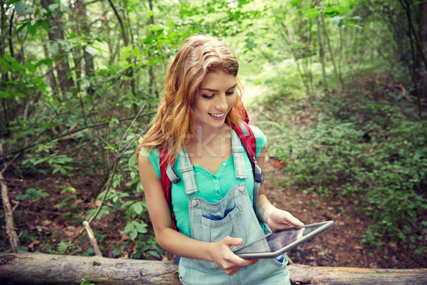 happy woman with backpack and tablet pc in woods Stock photo © dolgachov