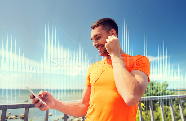 smiling young man with smartphone and earphones Stock photo © dolgachov