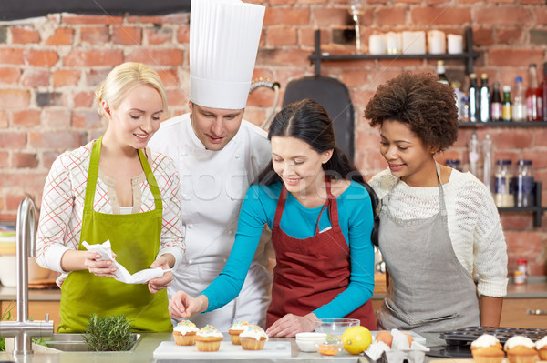 happy women and chef cook cooking in kitchen Stock photo © dolgachov