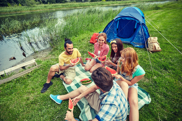 happy friends eating watermelon at camping Stock photo © dolgachov