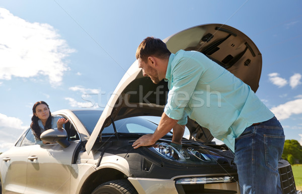 couple with open hood of broken car at countryside Stock photo © dolgachov