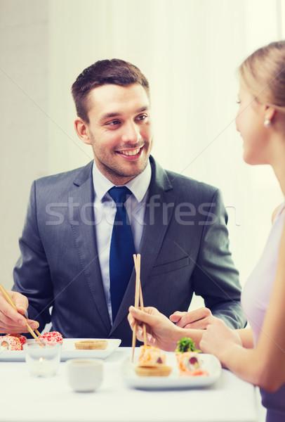 smiling couple eating sushi at restaurant Stock photo © dolgachov