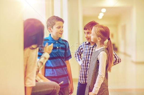 group of smiling school kids talking in corridor Stock photo © dolgachov